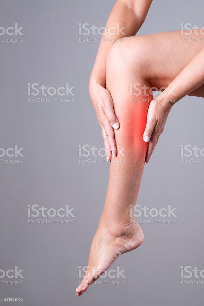 Massage of female leg on a gray background stock photo