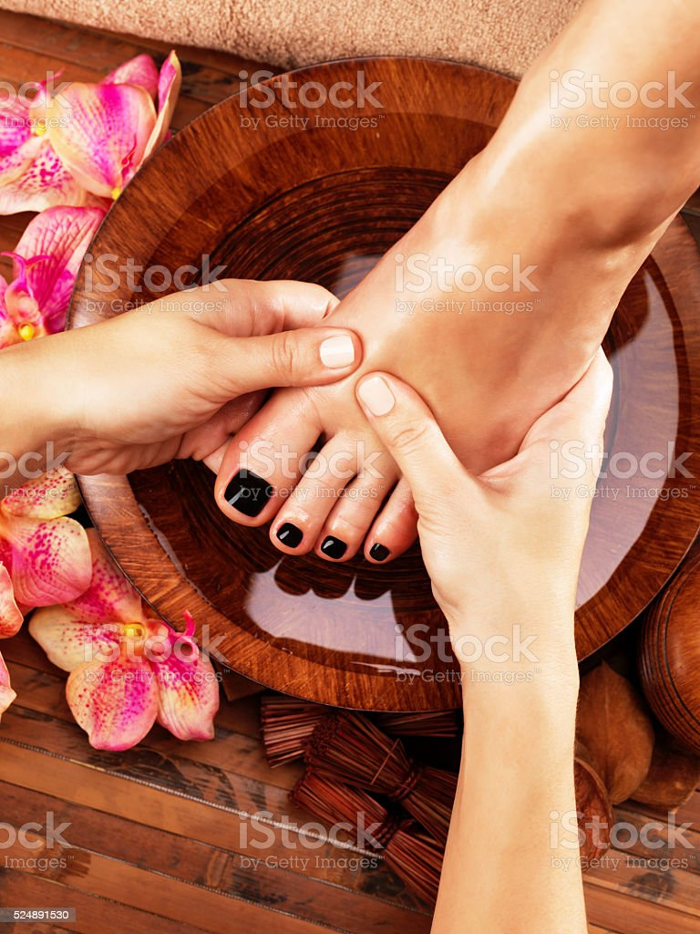 Massage of woman's foot in spa salon stock photo