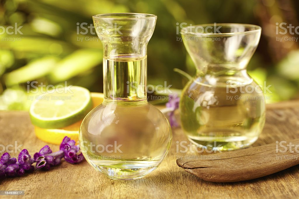 Massage oil bottles at spa with lemon an purple flowers stock photo