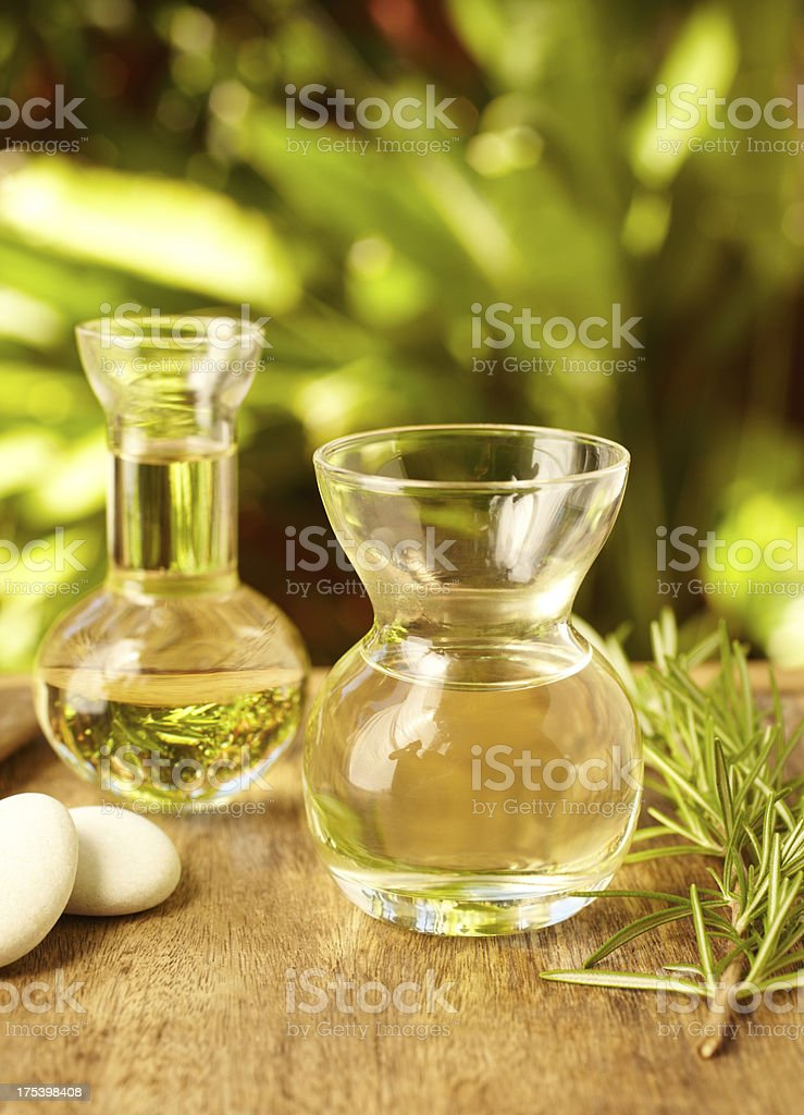 Massage oil bottles at spa with pebble stones royalty-free stock photo