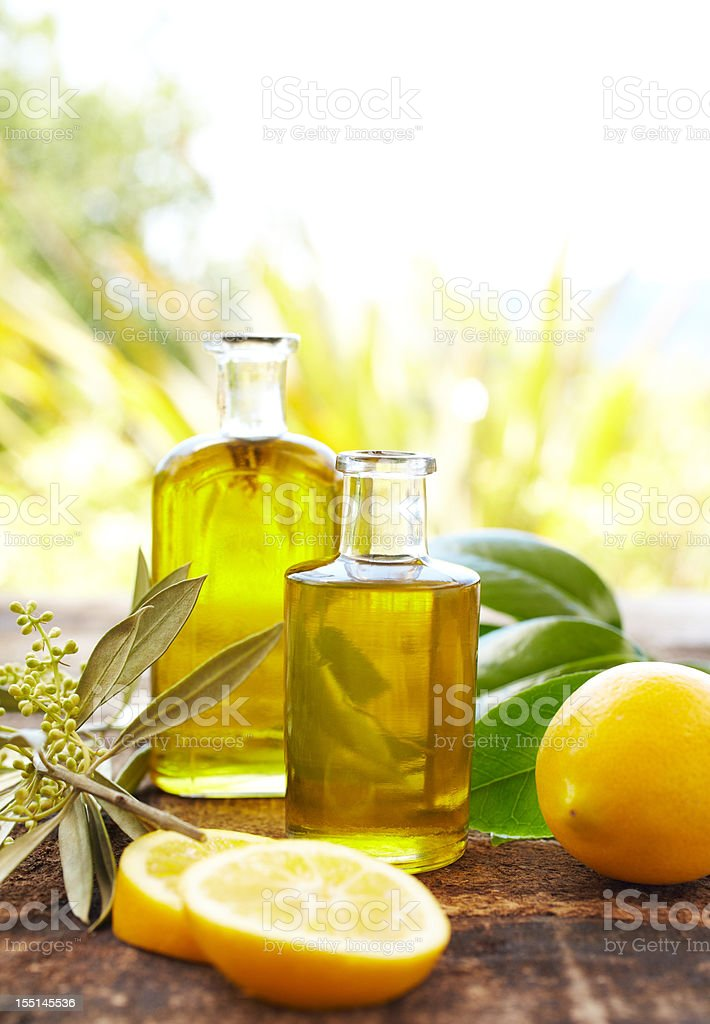 Massage oil bottles with lemons and leaves at spa outdoors stock photo