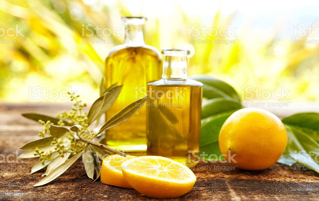 Massage oil bottles with lemons and olive branch stock photo