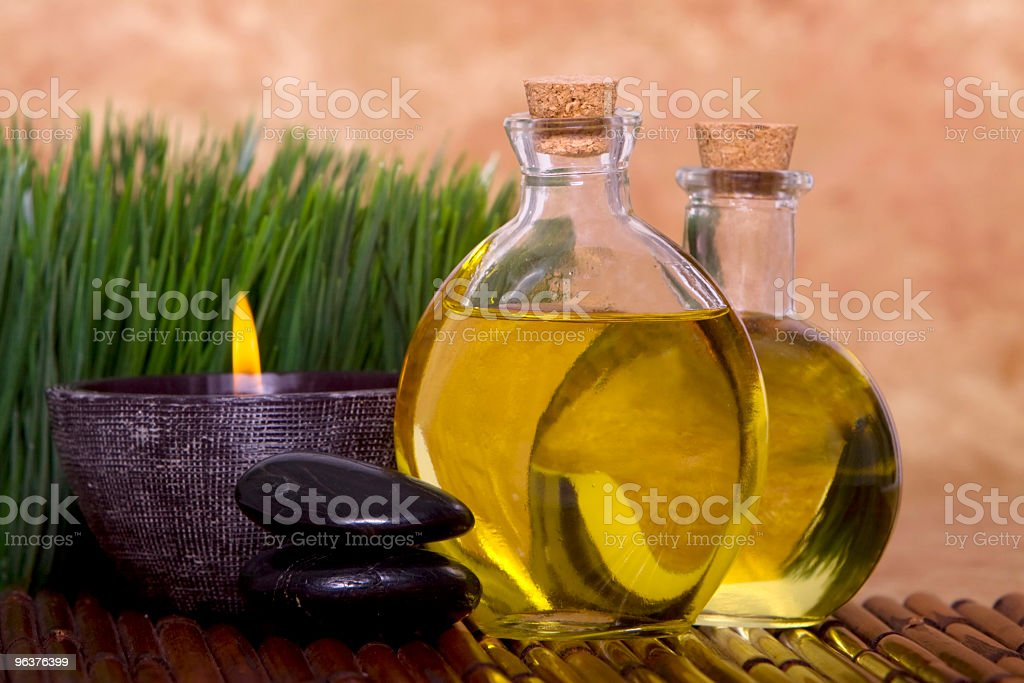 Massage oils and candle with green grass royalty-free stock photo