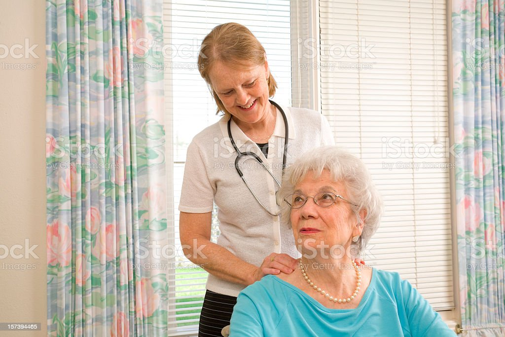 Massage physical therapist attends to senior woman, home healthcare stock photo