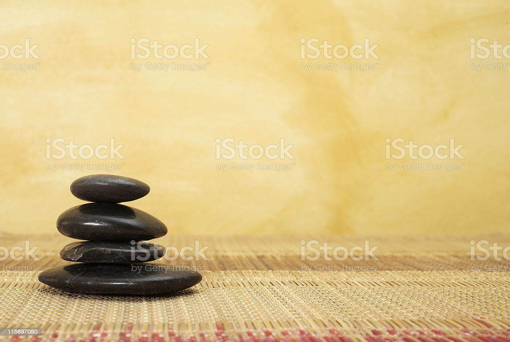 massage rocks on woven bamboo grass mat stock photo