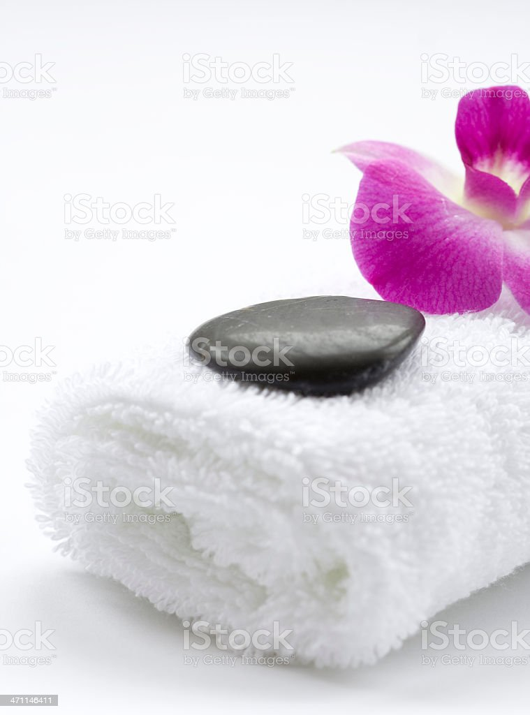 Massage stone with towel and beautiful pink Orchid flower royalty-free stock photo