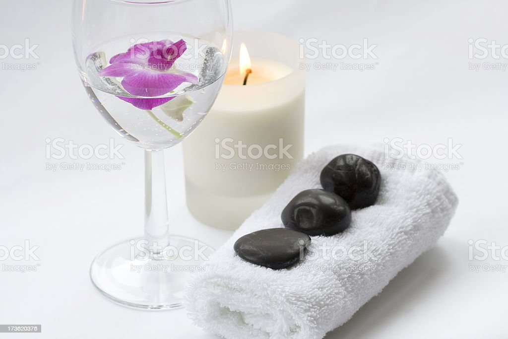 Massage stones and Pink Orchid in glass of water royalty-free stock photo