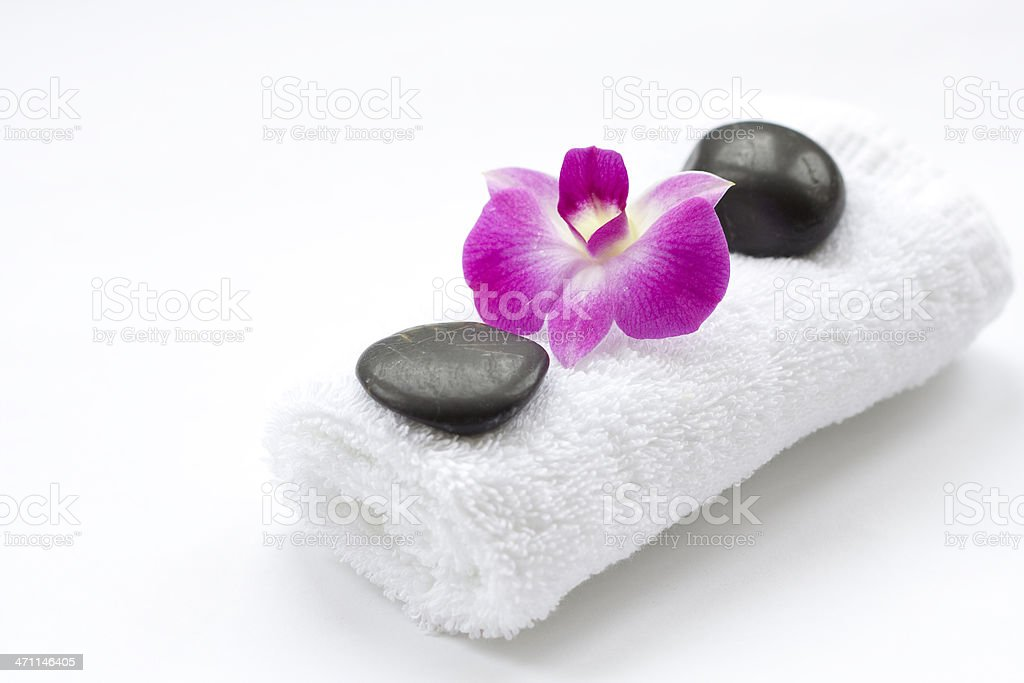 Massage stones with towel and beautiful pink Orchid flower royalty-free stock photo