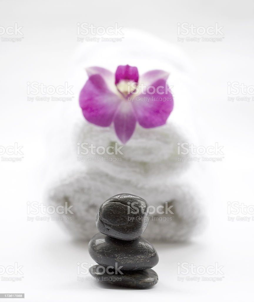 Massage stones with towels and beautiful pink Orchid flower royalty-free stock photo