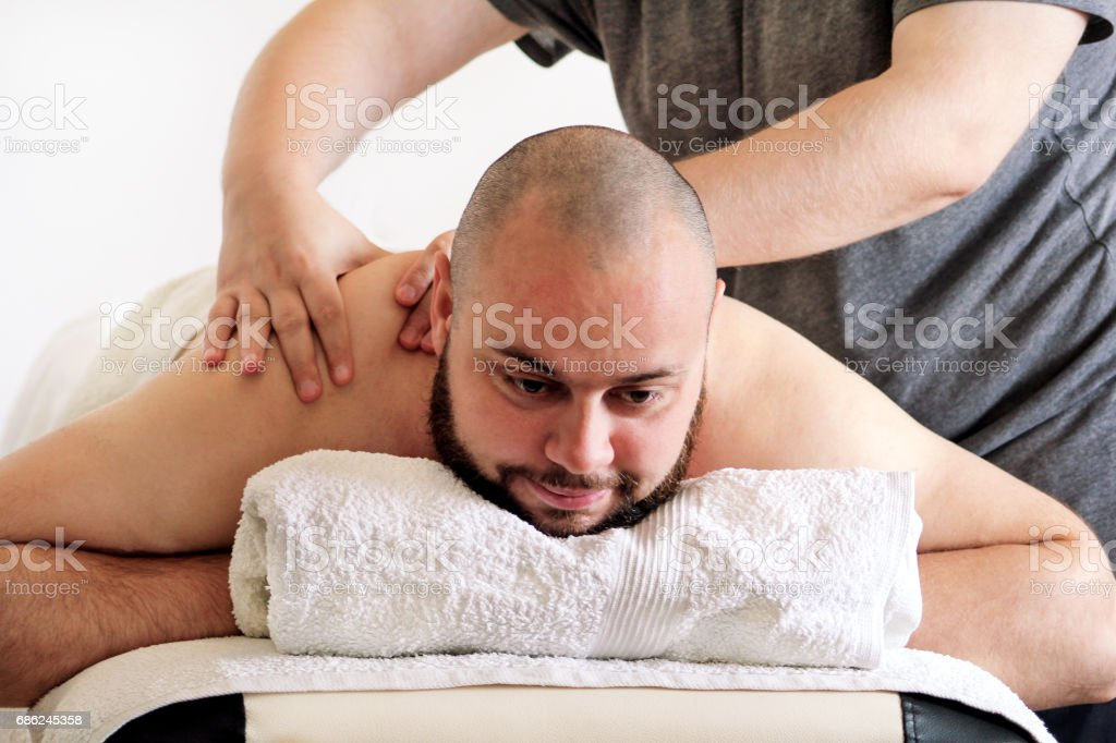 Massage studio. Sports massage. Massage therapist massaging shoulders of a male athlete, working with neck muscles. Body care. Man having massage in the spa body massage salon. Massage table. stock photo