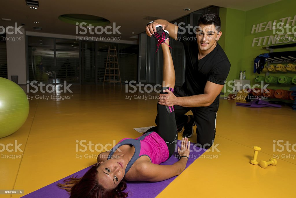 Massage therapist helps her client into a stretching pose stock photo