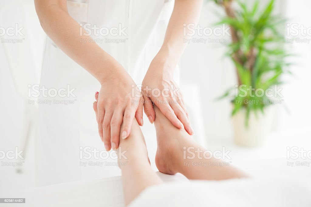 Massage therapist touching the foot of a woman stock photo