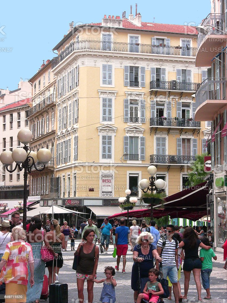 Massena street coming from the namesake square on a summer's day with sun, a lot of people some in the foreground, several resognisable, and some shop signs stock photo