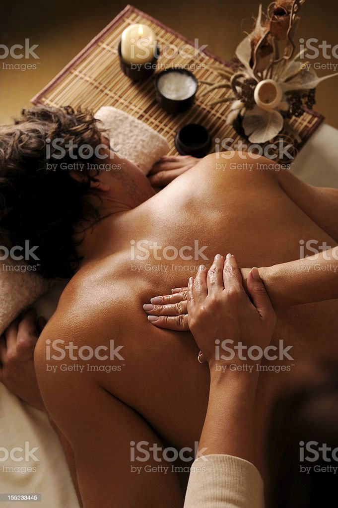 masseur does back massage to the young man royalty-free stock photo