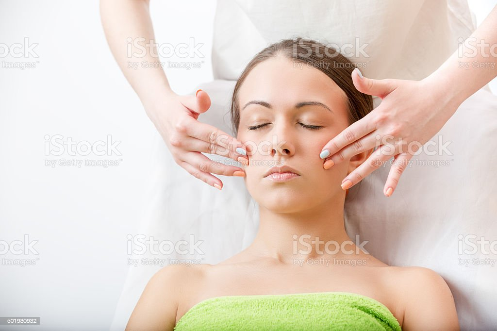 masseur makes massage of the face brunette stock photo