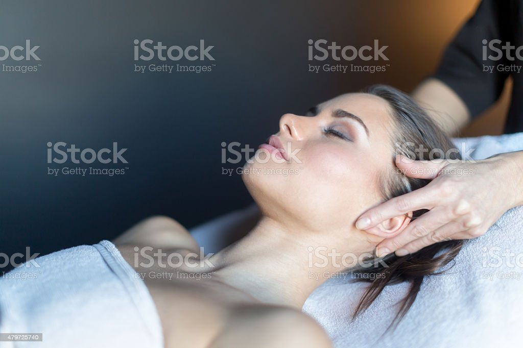 Masseur massaging face of a beautiful, young woman stock photo
