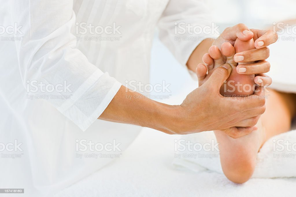 Masseur massaging human leg at spa royalty-free stock photo