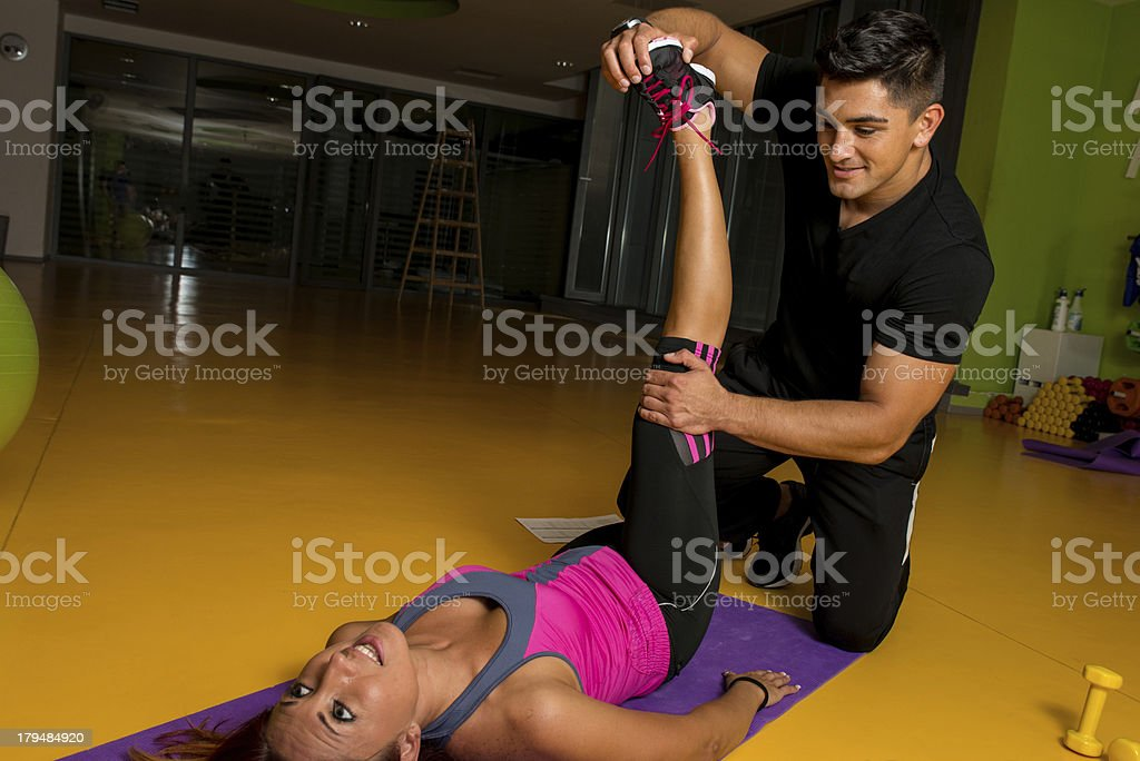 Masseur stretching woman's leg stock photo