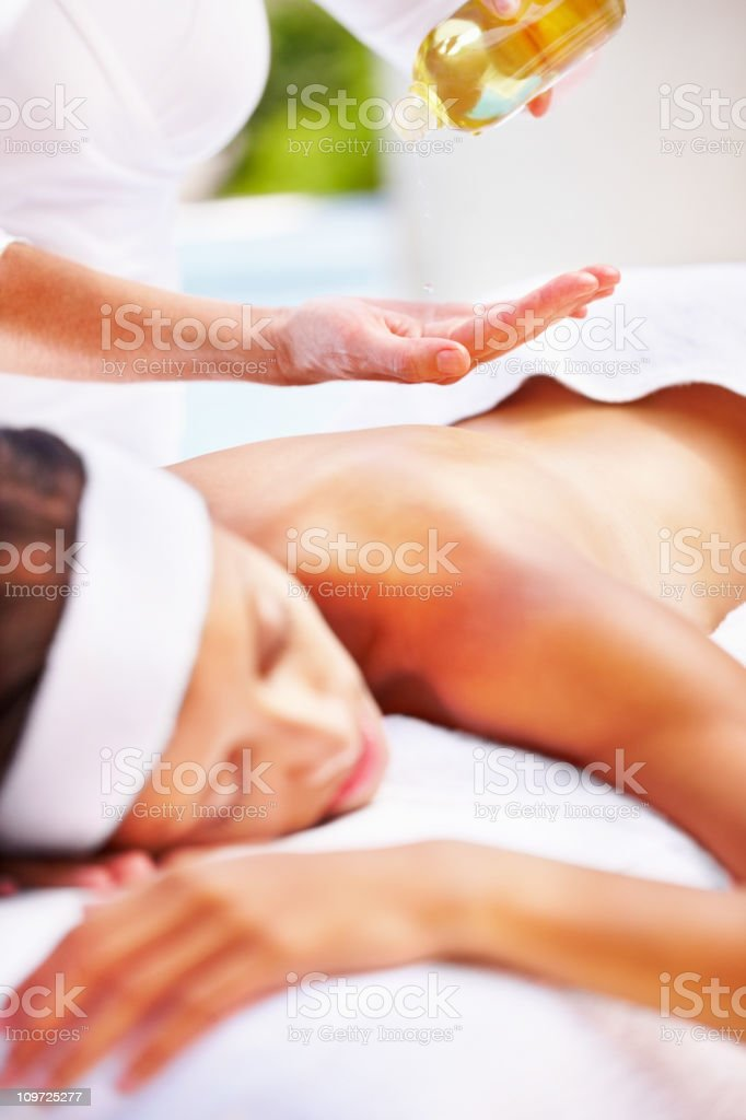 Masseuse using an oil to massage a woman's back royalty-free stock photo