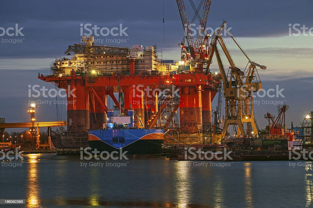 Massive oil rig facilities along shore at sunset stock photo