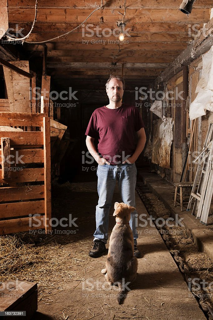 Master and his dog in a barn royalty-free stock photo