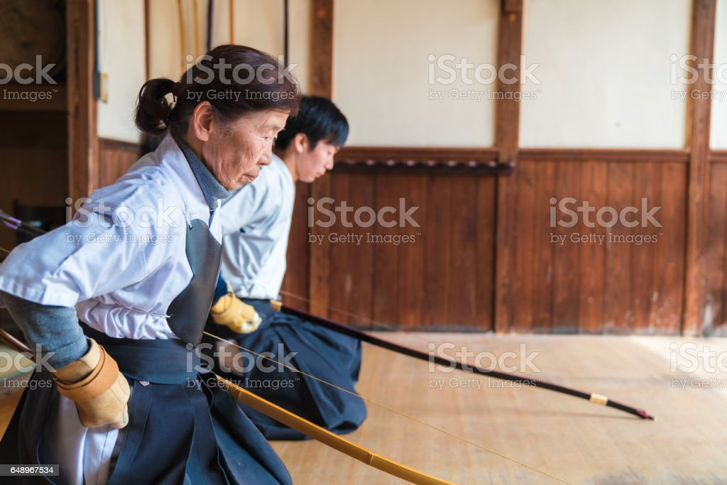 Master archer and her student pausing to show respect stock photo