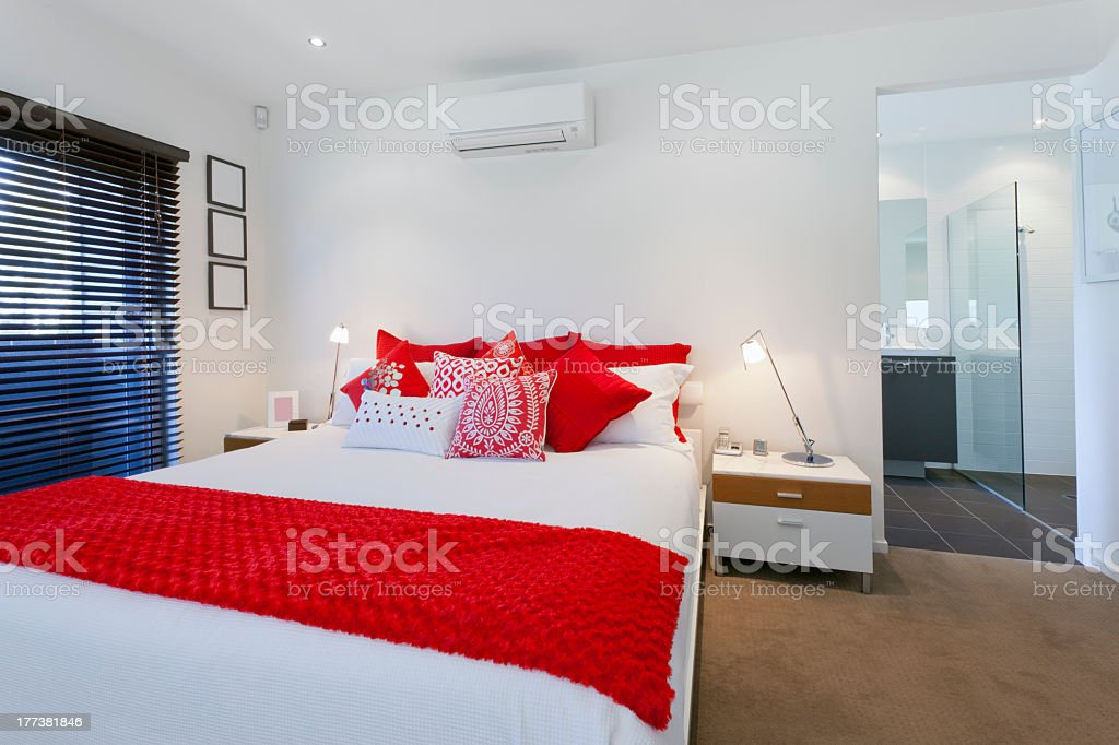 Master bedroom decorated in white with red accents stock photo