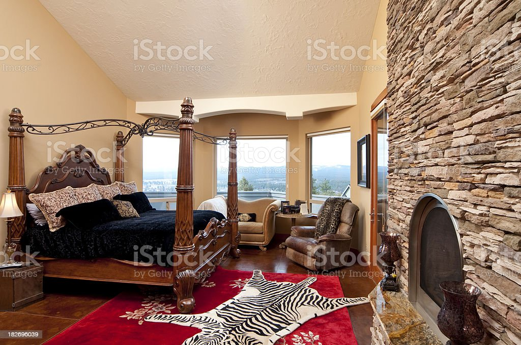 Master bedroom with brick wall fireplace royalty-free stock photo