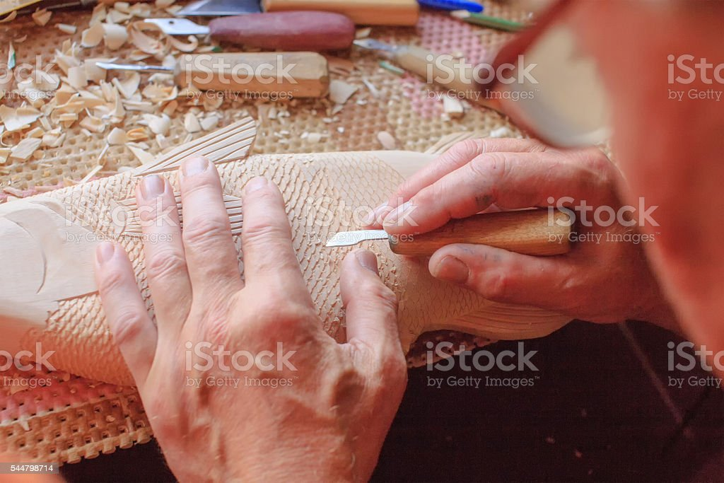 master carves wooden fish stock photo