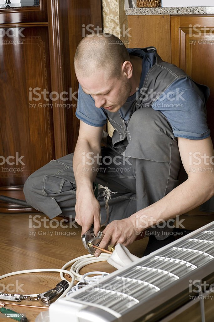 Master electrician prepares to install new air conditioner royalty-free stock photo