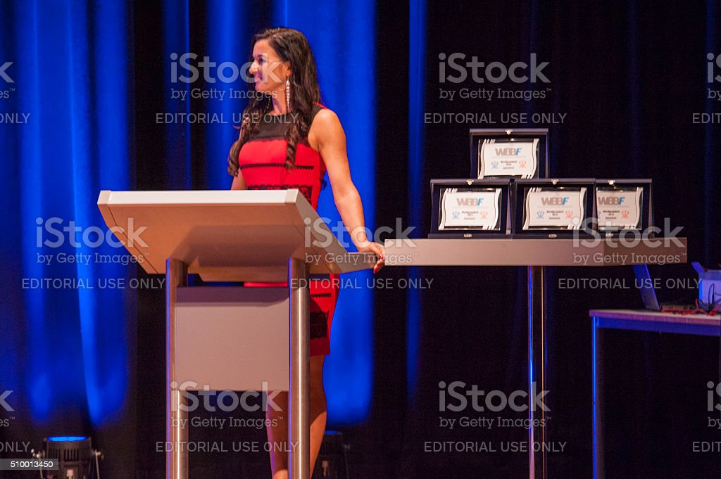 Master of ceremonies behind pulpit addresses theatre crowd with stock photo