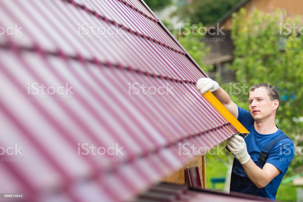 master on repair of roofs makes measurements tool stock photo