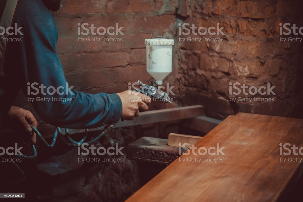 Master painter in a factory - industrial painting  wood with spray gun. Soft focus. Shallow DOF. stock photo