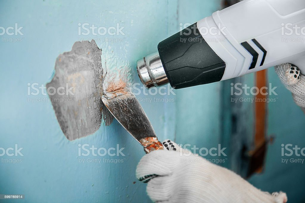 Master removes old paint concrete wall heat gun and scraper stock photo