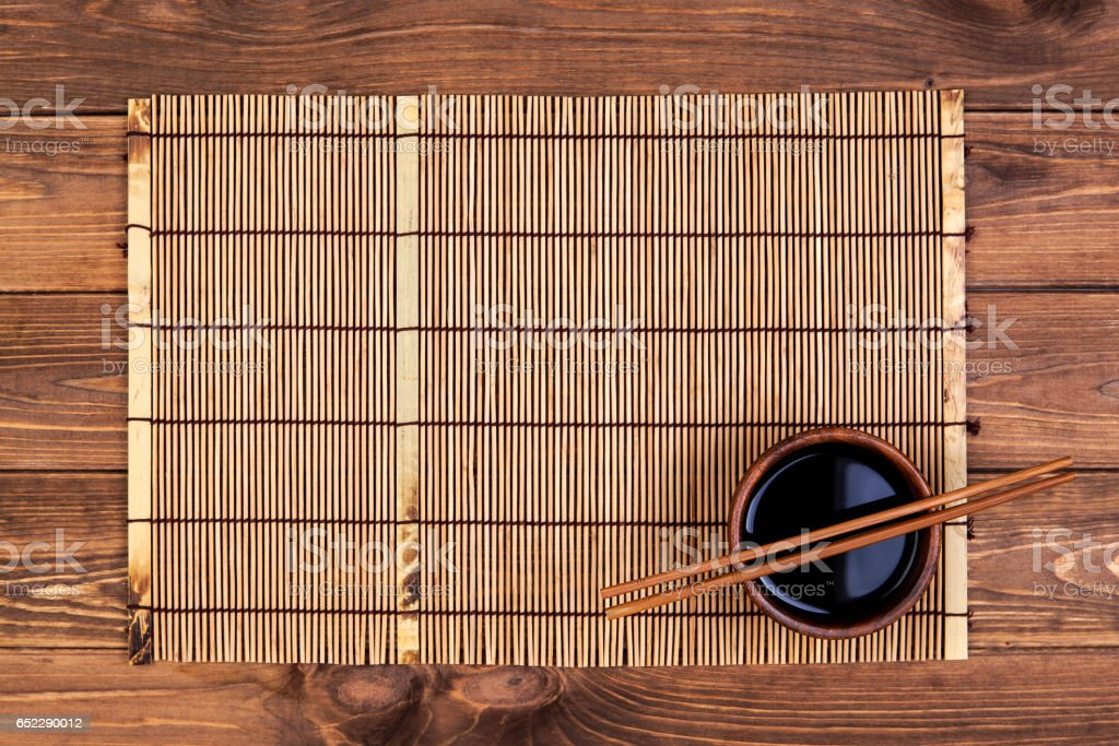 Mat for sushi and chopsticks on wooden background. Top view with copy space stock photo