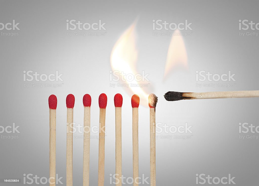 A match lighting the rest of the red matches stock photo