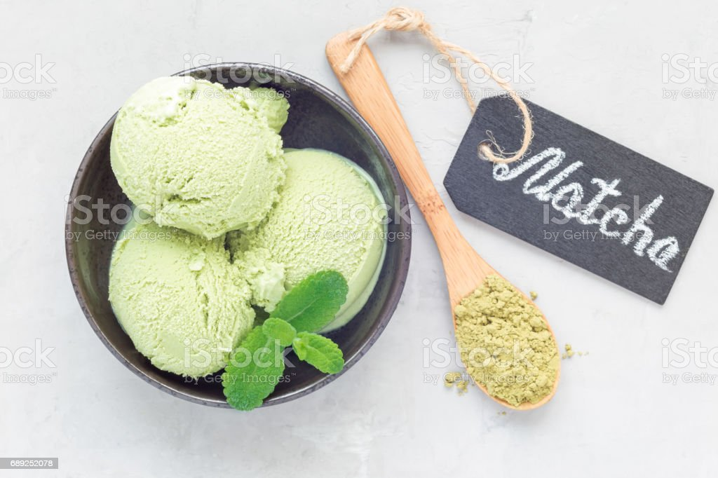 Matcha green tea ice cream balls in black bowl, horizontal, top view stock photo