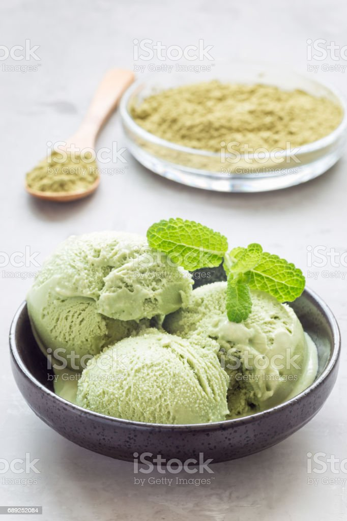 Matcha green tea ice cream balls in black bowl, vertical stock photo