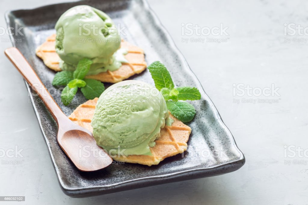 Matcha green tea ice cream balls served with waffles on black plate, horizontal, copy space stock photo