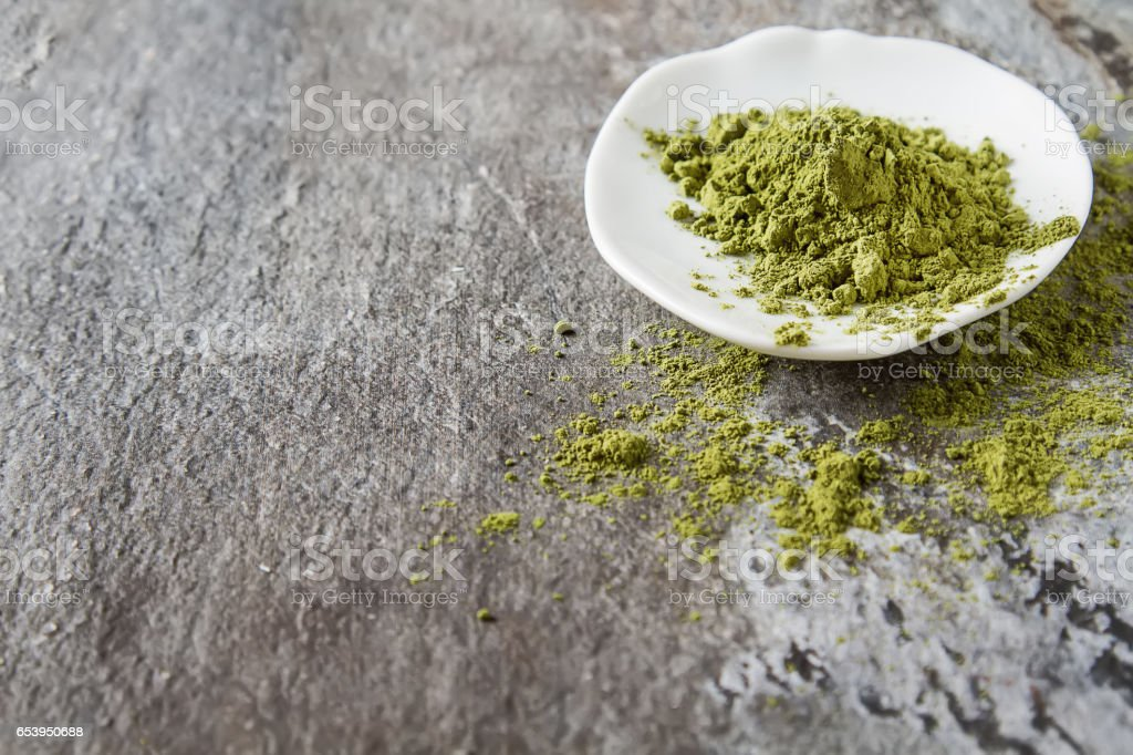 Matcha tea on a small white plate. Gray background. stock photo