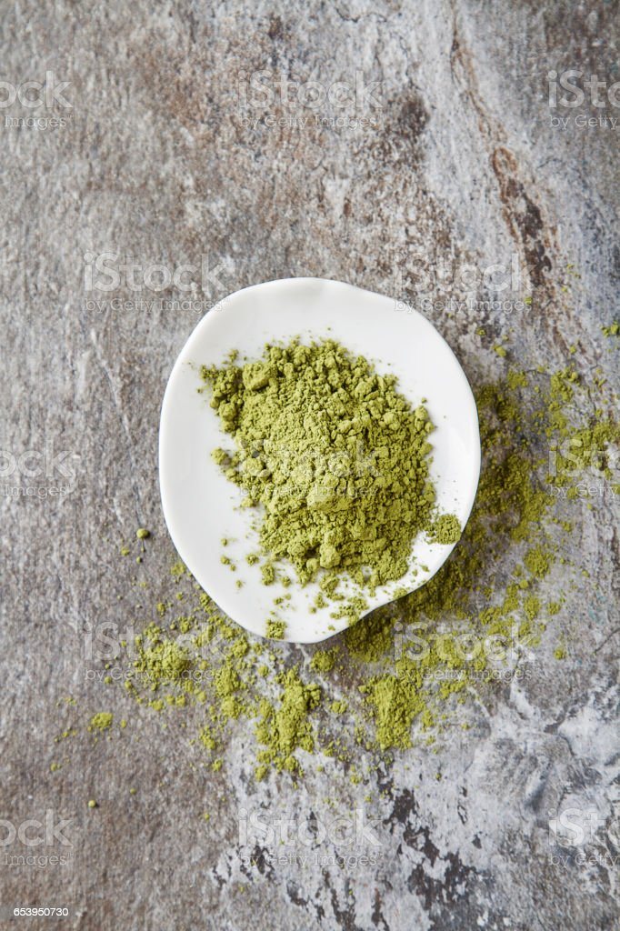 Matcha tea on a small white plate. Gray background. Top view stock photo