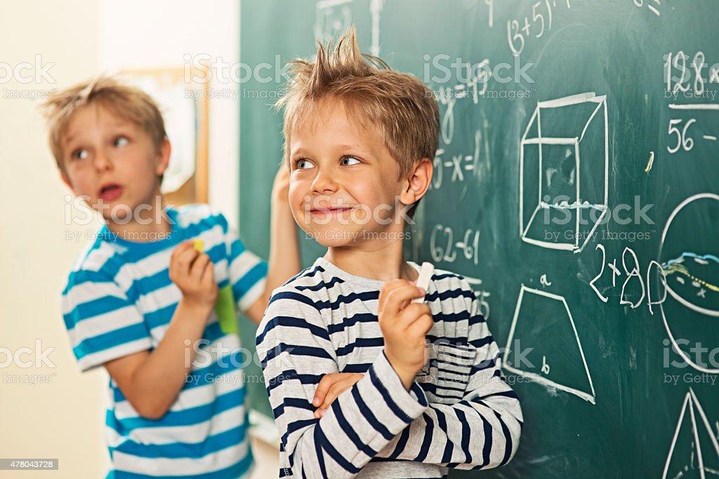 Math is fun - boys standing at the blackboard stock photo