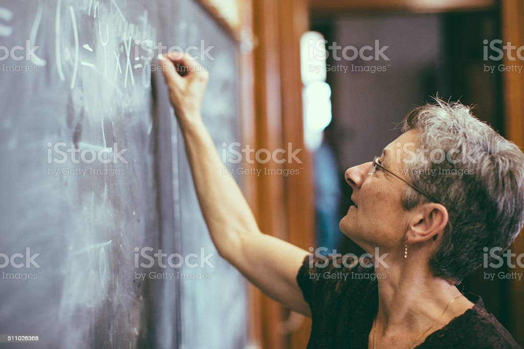 Mathemathics professor at chalkboard writing formula stock photo
