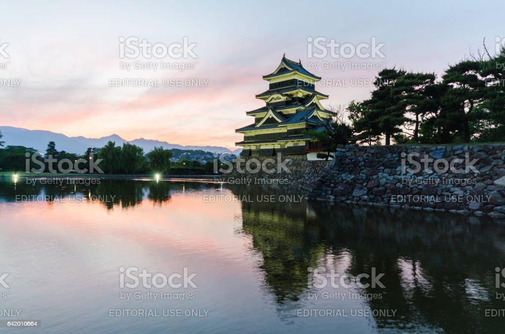 Matsumoto castle and sunset sky reflect on water at nagano japan stock photo
