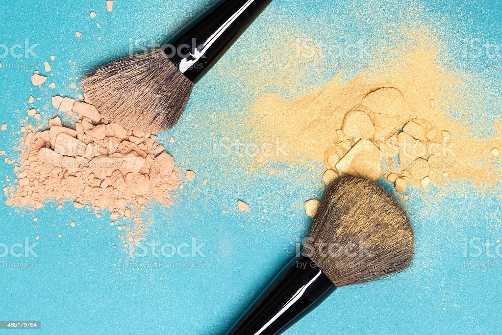 Matte compact powder and shimmer powder with makeup brushes stock photo