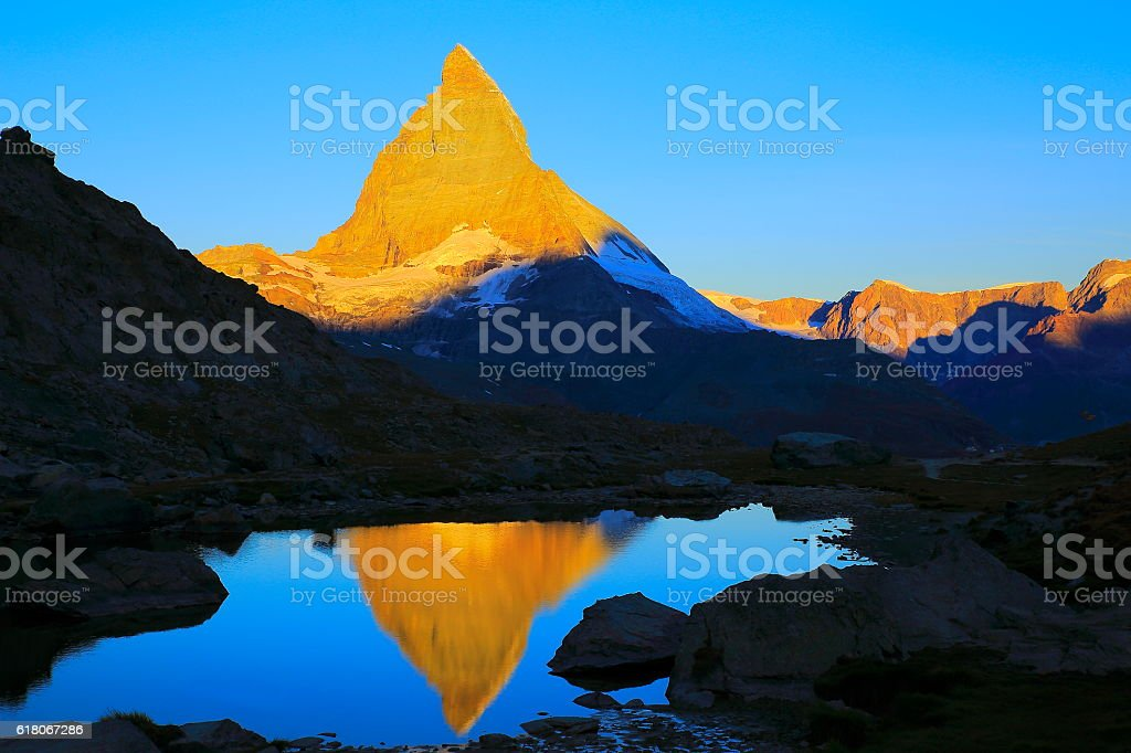 Matterhorn mirrored lake reflection, peaceful sunrise landscape, Swiss Alps stock photo