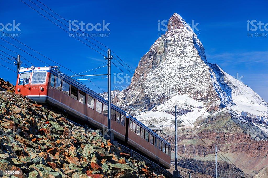 Matterhorn peak against  train in Swiss Alps stock photo