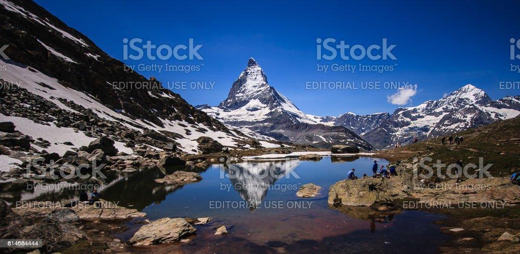 Matterhorn Peak reflection in summer at Riffelsee lake, Gornergrat station, Zermatt, Switzerland. stock photo