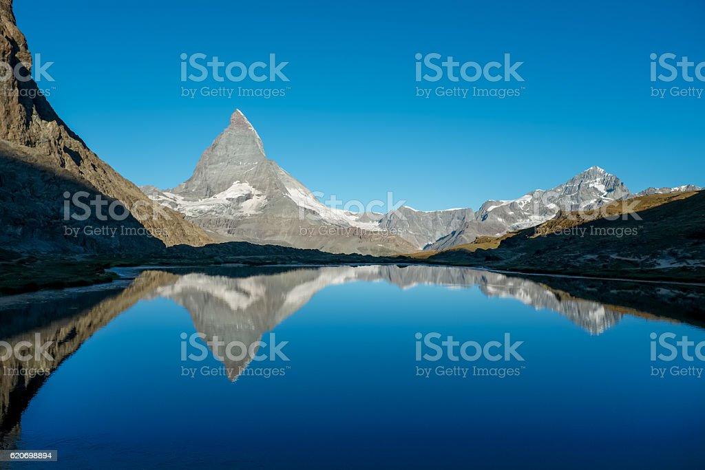 Matterhorn reflected in lake Riffelsee against crisp blue sky stock photo