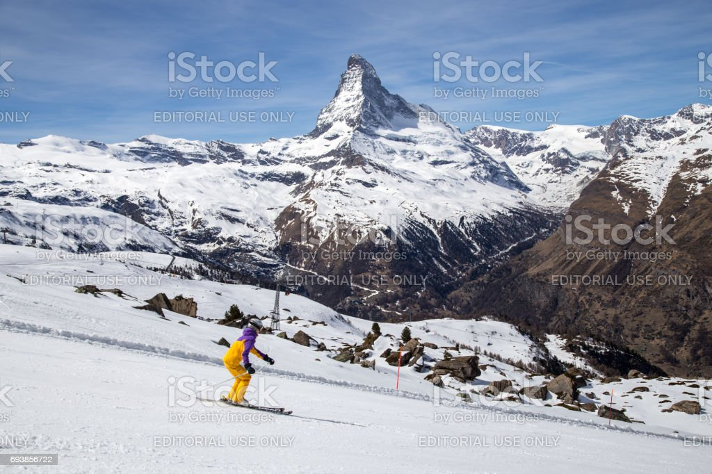 A young woman skiing in front of the famous Matterhorn
